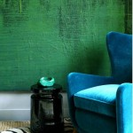 blue velvet chair and green wall