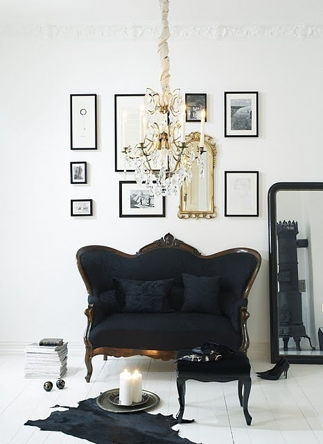 beautiful vintage black settee a collection of frames decorate the
